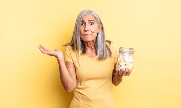 Ładna kobieta w średnim wieku czuje się zakłopotana, zdezorientowana i wątpi. koncepcja butelki cukierków