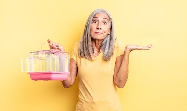 Ładna kobieta w średnim wieku czuje się zakłopotana, zdezorientowana i wątpi. koncepcja klatki dla zwierząt lub więzienia