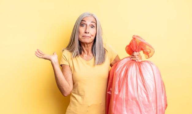 Ładna kobieta w średnim wieku czuje się zakłopotana, zdezorientowana i wątpi. plastikowa torba garbaje