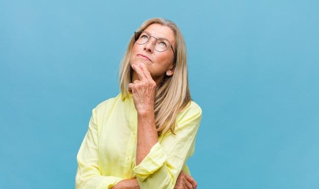 Ładna kobieta w średnim wieku czuje się zamyślona, zastanawia się lub wyobraża sobie pomysły, marzy na jawie i patrzy w górę, aby skopiować przestrzeń