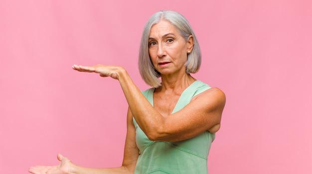 Ładna kobieta w średnim wieku czuje się zestresowana i niespokojna, przygnębiona i sfrustrowana bólem głowy, podnosząca obie ręce do głowy