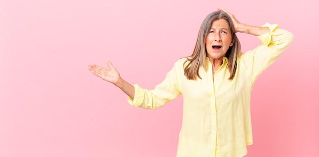 Ładna kobieta w średnim wieku czuje się zestresowana, niespokojna lub przestraszona, z rękami na głowie