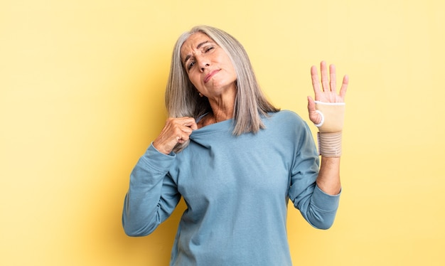 Ładna kobieta w średnim wieku czuje się zestresowana, niespokojna, zmęczona i sfrustrowana. koncepcja bandaża ręcznego