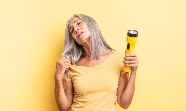 Ładna kobieta w średnim wieku czuje się zestresowana, niespokojna, zmęczona i sfrustrowana. koncepcja latarki