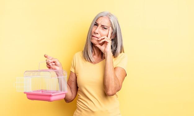 Ładna kobieta w średnim wieku czuje się znudzona, sfrustrowana i senna po męczącym dniu. koncepcja klatki dla zwierząt lub więzienia