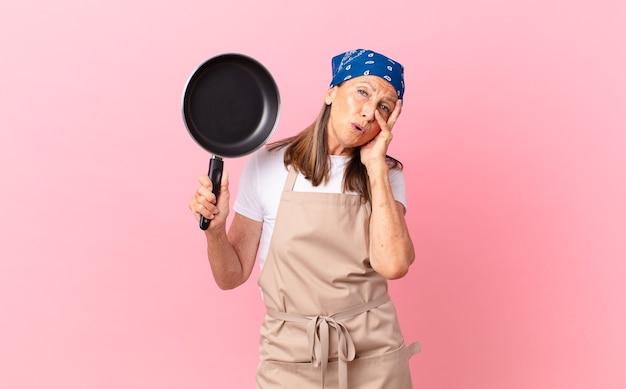 Ładna kobieta w średnim wieku czuje się znudzona, sfrustrowana i senna po męczącym i trzymaniu patelni. koncepcja szefa kuchni