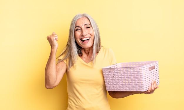 Ładna kobieta w średnim wieku czuje się zszokowana, śmieje się i świętuje sukces. koncepcja pustego koszyka