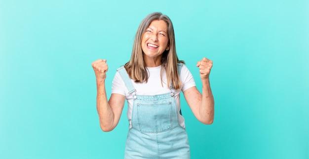 Ładna kobieta w średnim wieku czuje się zszokowana, śmieje się i świętuje sukces