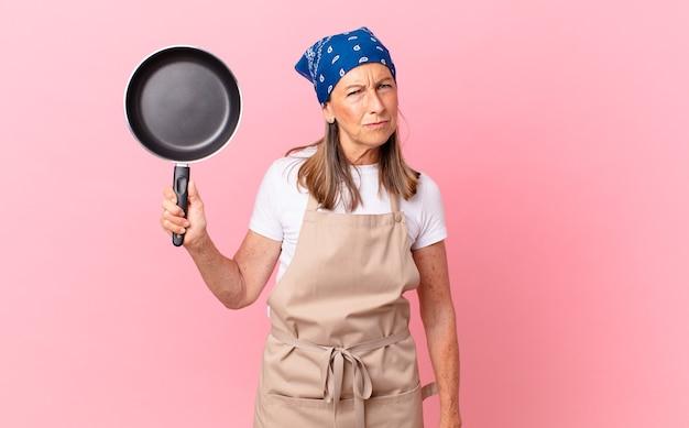 Ładna kobieta w średnim wieku, która czuje się smutna, zdenerwowana lub zła, patrzy w bok i trzyma patelnię. koncepcja szefa kuchni