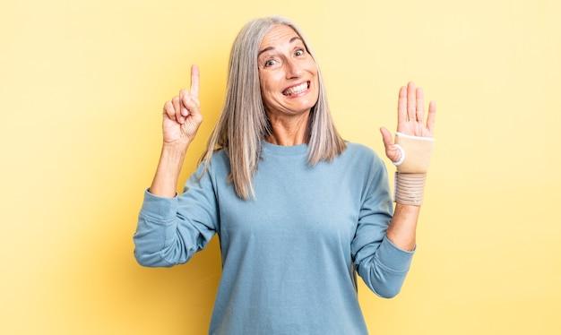 Ładna kobieta w średnim wieku, która po zrealizowaniu pomysłu czuje się jak szczęśliwy i podekscytowany geniusz. koncepcja bandaża ręcznego