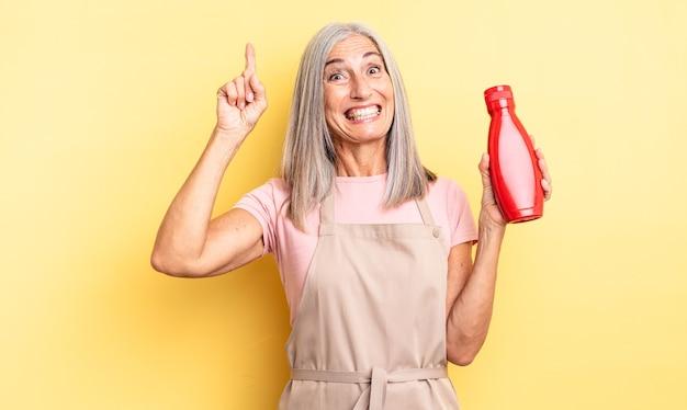 Ładna kobieta w średnim wieku, która po zrealizowaniu pomysłu czuje się jak szczęśliwy i podekscytowany geniusz. koncepcja ketchupu