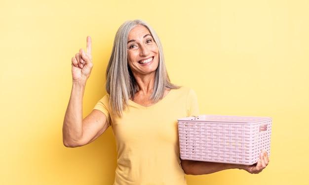 Ładna kobieta w średnim wieku, która po zrealizowaniu pomysłu czuje się jak szczęśliwy i podekscytowany geniusz. koncepcja pustego koszyka