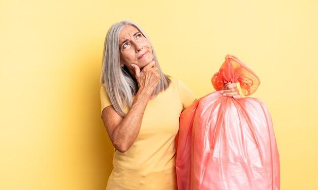 Ładna kobieta w średnim wieku myśli, wątpi i jest zdezorientowana. plastikowa torba garbaje