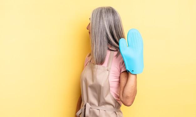 Ładna kobieta w średnim wieku na widoku profilu myśląca, wyobrażająca sobie lub marząca na jawie. koncepcja rękawic kuchennych