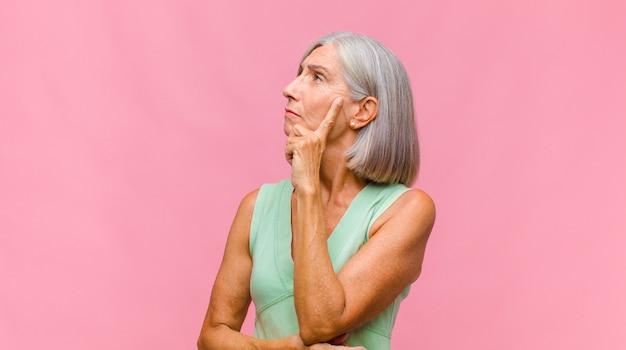 Ładna kobieta w średnim wieku o poważnym i skoncentrowanym spojrzeniu, burzy mózgów i myśląca o trudnym problemie