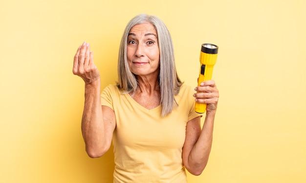 Ładna kobieta w średnim wieku robiąca gest kaprysu lub pieniędzy, mówiąca, że musisz zapłacić. koncepcja latarki