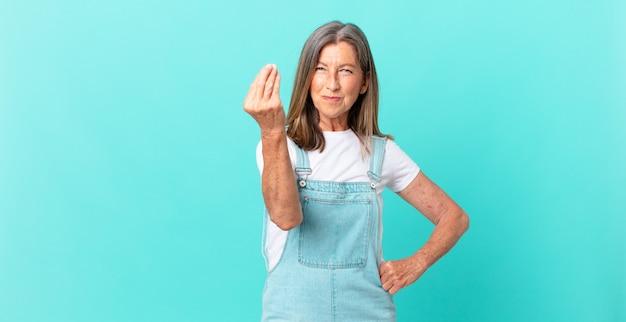 Ładna kobieta w średnim wieku robiąca gest kaprysu lub pieniędzy, mówiąca, żebyś zapłaciła