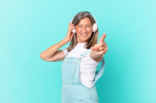 Ładna kobieta w średnim wieku słucha muzyki przez słuchawki