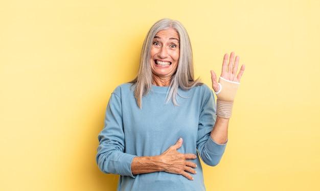 Ładna kobieta w średnim wieku śmiejąca się głośno z jakiegoś przezabawnego żartu. koncepcja bandaża ręcznego