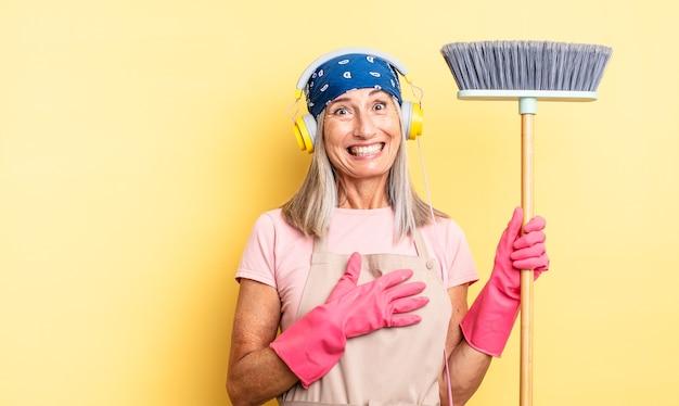 Ładna kobieta w średnim wieku śmiejąca się głośno z jakiegoś przezabawnego żartu. koncepcja gospodarstwa domowego i miotły