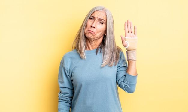 Ładna kobieta w średnim wieku, smutna i jęcząca, z nieszczęśliwym spojrzeniem i płaczem. koncepcja bandaża ręcznego