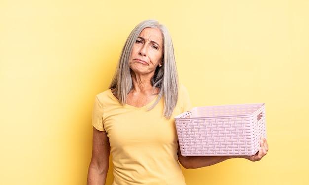 Ładna kobieta w średnim wieku, smutna i jęcząca, z nieszczęśliwym spojrzeniem i płaczem. koncepcja pustego koszyka