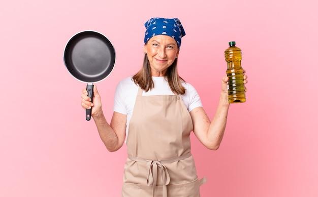 Ładna kobieta w średnim wieku trzymająca patelnię i butelkę oliwy z oliwek?