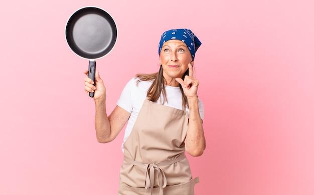 Ładna kobieta w średnim wieku uśmiecha się radośnie i marzy lub wątpi i trzyma patelnię. koncepcja szefa kuchni
