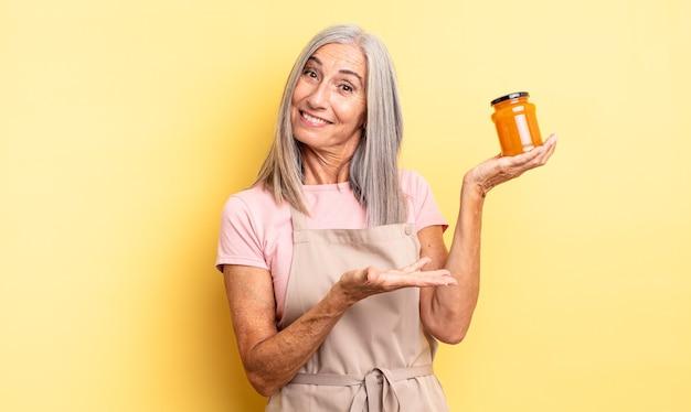 Ładna kobieta w średnim wieku, uśmiechając się radośnie, czując się szczęśliwa i pokazując koncepcję. dżem brzoskwiniowy