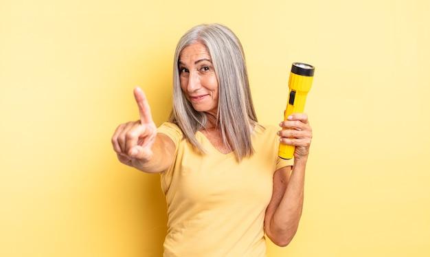 Ładna kobieta w średnim wieku uśmiechnięta dumnie i pewnie robiąc numer jeden. koncepcja latarki