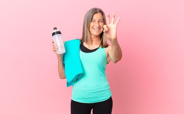Ładna kobieta w średnim wieku, uśmiechnięta i patrząca przyjaźnie, pokazując numer trzy. koncepcja fitness
