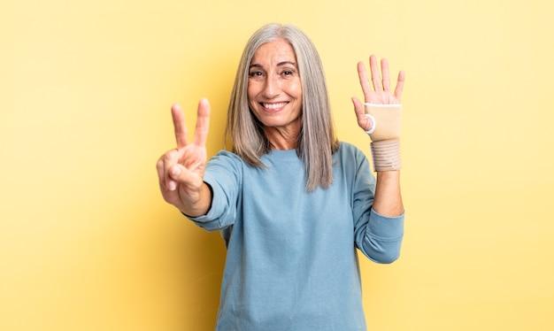 Ładna kobieta w średnim wieku, uśmiechnięta i wyglądająca przyjaźnie, pokazując numer dwa. koncepcja bandaża ręcznego