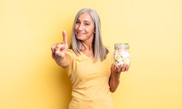 Ładna kobieta w średnim wieku, uśmiechnięta i wyglądająca przyjaźnie, pokazując numer jeden. koncepcja butelki cukierków