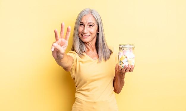 Ładna kobieta w średnim wieku, uśmiechnięta i wyglądająca przyjaźnie, pokazując numer trzy. koncepcja butelki cukierków