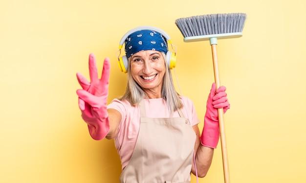Ładna kobieta w średnim wieku, uśmiechnięta i wyglądająca przyjaźnie, pokazując numer trzy. koncepcja gospodarstwa domowego i miotły