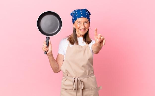 Ładna kobieta w średnim wieku uśmiechnięta i wyglądająca przyjaźnie, pokazująca numer jeden i trzymająca patelnię. koncepcja szefa kuchni