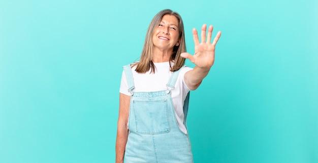 Ładna kobieta w średnim wieku, uśmiechnięta i wyglądająca przyjaźnie, pokazująca numer pięć