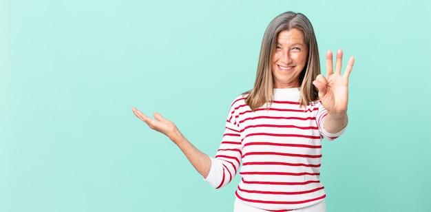 Ładna kobieta w średnim wieku, uśmiechnięta i wyglądająca przyjaźnie, pokazująca numer trzy