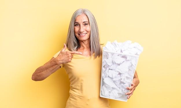 Ładna kobieta w średnim wieku, uśmiechnięta radośnie, czująca się szczęśliwa i wskazująca na bok. koncepcja awarii kulek papierowych