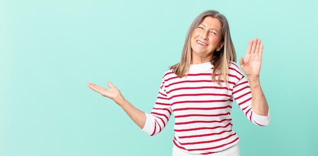 Ładna kobieta w średnim wieku, uśmiechnięta radośnie, machająca ręką, witająca i witająca cię