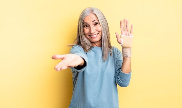 Ładna kobieta w średnim wieku uśmiechnięta radośnie z przyjaznym i oferującym i pokazującym koncepcję. koncepcja bandaża ręcznego