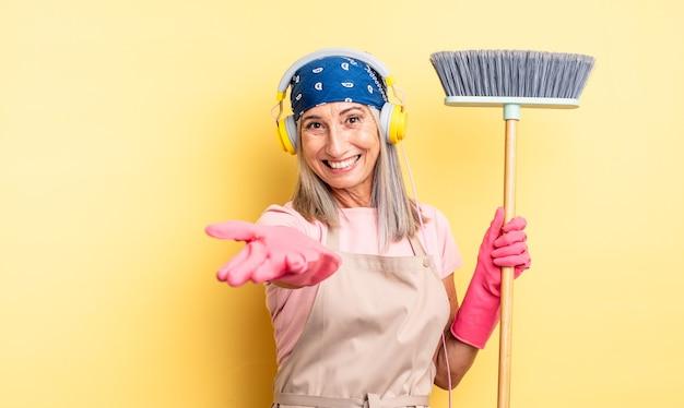 Ładna kobieta w średnim wieku uśmiechnięta radośnie z przyjaznym i oferującym i pokazującym koncepcję. koncepcja gospodarstwa domowego i miotły