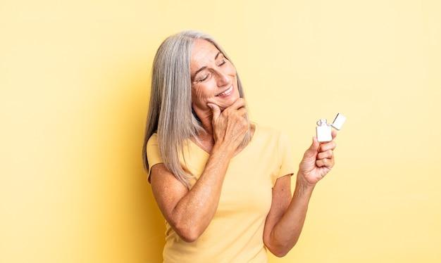 Ładna kobieta w średnim wieku uśmiechnięta ze szczęśliwym, pewnym siebie wyrazem twarzy z ręką na brodzie. lżejsza koncepcja