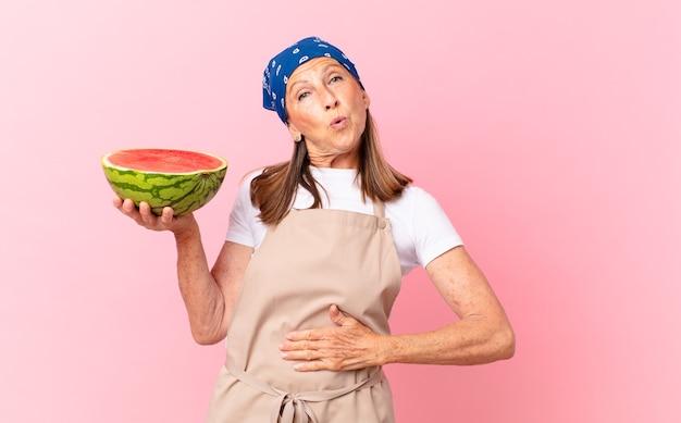 Ładna kobieta w średnim wieku w fartuchu i trzymająca arbuza
