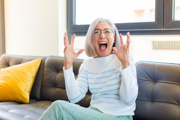 Ładna kobieta w średnim wieku wściekle krzyczy, czuje się zestresowana i zirytowana, z rękami uniesionymi do góry, mówiąc, dlaczego ja