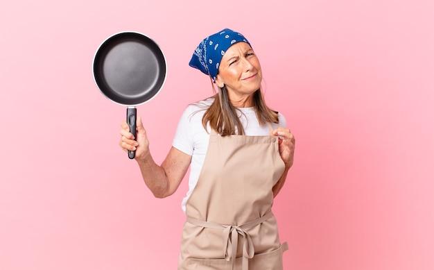 Ładna kobieta w średnim wieku wyglądająca arogancko, odnosząca sukcesy, pozytywna i dumna, trzymająca patelnię. koncepcja szefa kuchni