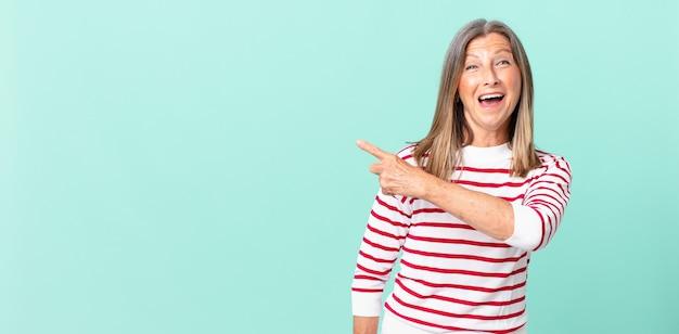 Ładna kobieta w średnim wieku, wyglądająca na podekscytowaną i zaskoczoną, wskazując na bok