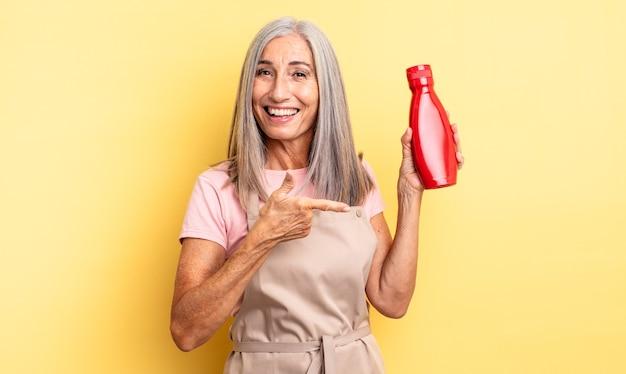 Ładna kobieta w średnim wieku wyglądająca na podekscytowaną i zdziwioną, wskazując na bok. koncepcja ketchupu