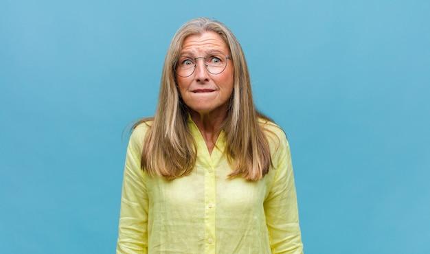Ładna kobieta w średnim wieku, wyglądająca na skoncentrowaną i intensywnie zastanawiająca się nad pomysłem, wyobrażająca sobie rozwiązanie wyzwania lub problemu