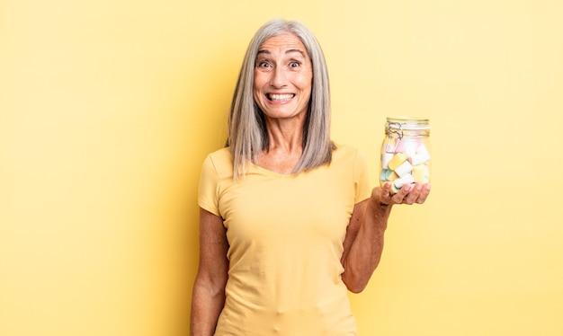 Ładna kobieta w średnim wieku wyglądająca na szczęśliwą i mile zaskoczoną. koncepcja butelki cukierków